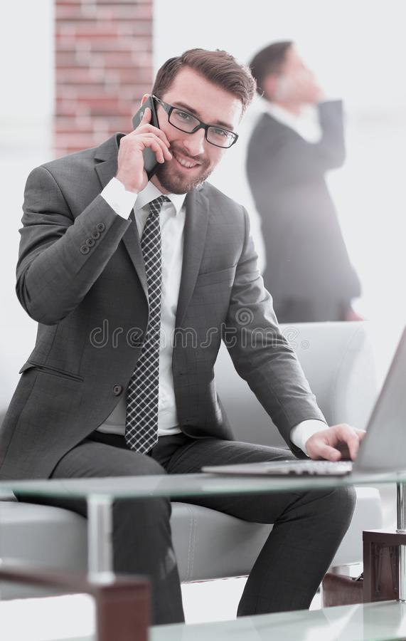 Image of young businessman talking on mobile phone with clients. Smiling men talking on mobile phone while using laptop computer at desk in study royalty free stock photo