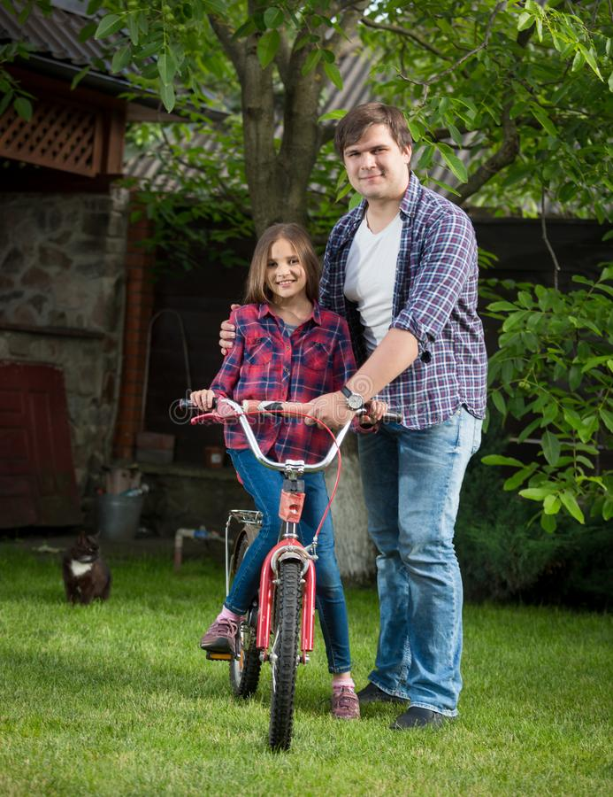 Smiling young man teaching his daughter riding bicycle at house backyard stock images