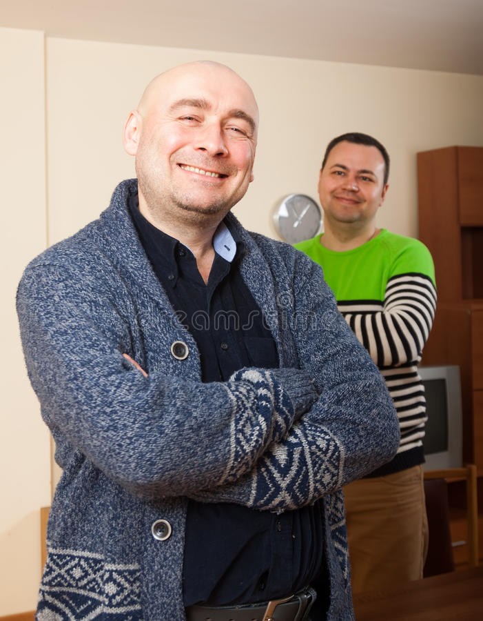 Smiling men. Two adult smiling men at home stock photography