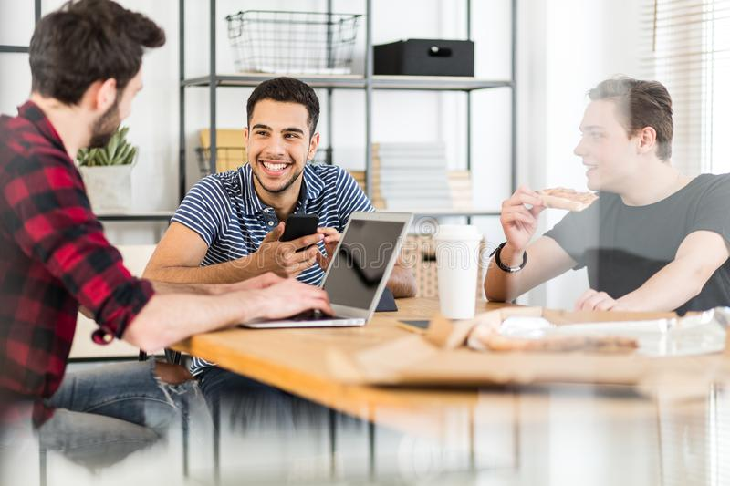Smiling man using smartphone while his friends eat pizza and use. Smiling men using smartphone while his friends eat pizza and use a laptop royalty free stock photography