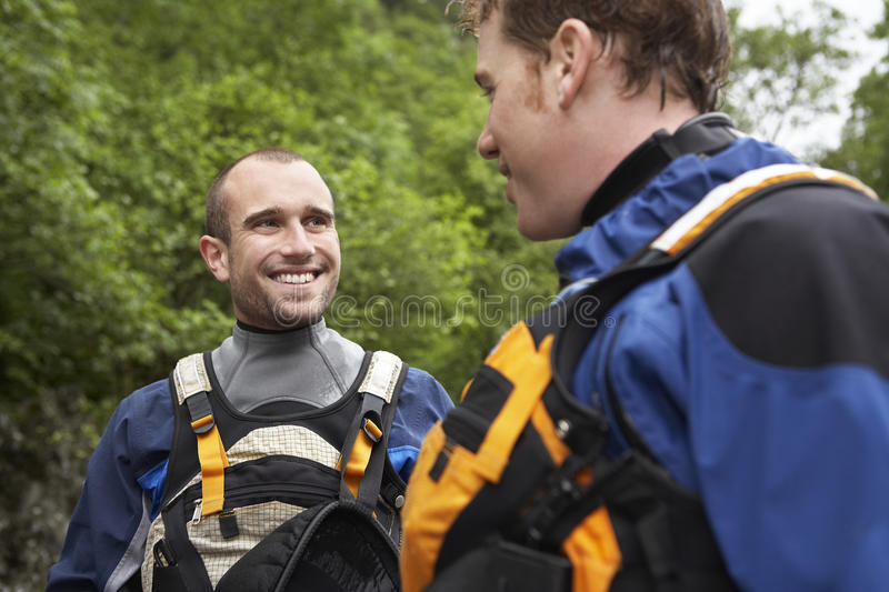 Smiling Men In Wetsuits. Two smiling young men in wetsuits outdoors stock photography