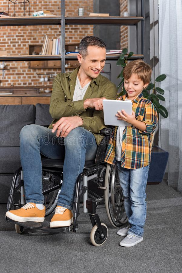 smiling man in wheelchair and little son using tablet together stock images