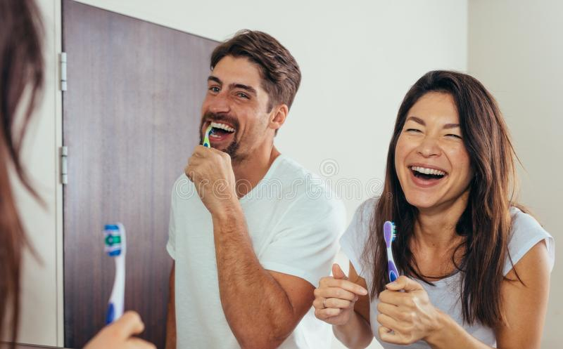 Smiling couple brushing teeth in bathroom stock photos