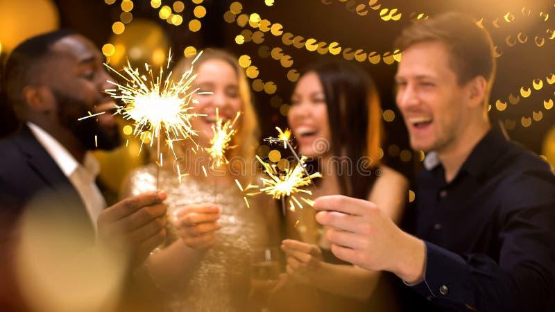Smiling men and women holding sparklers, festive atmosphere, luxury lifestyle. Stock photo royalty free stock photo