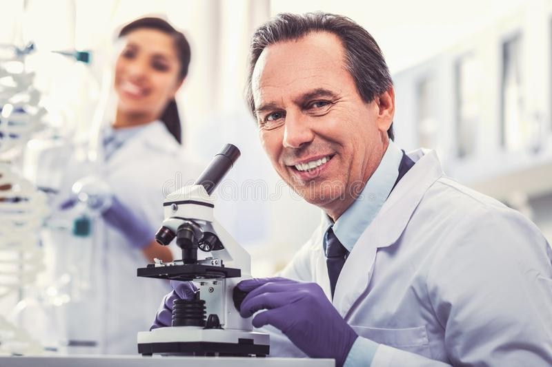 Smiling microbiologist making new discovery. New discovery. Smiling microbiologist wearing white uniform feeling impressed while making new revolutionary royalty free stock photography