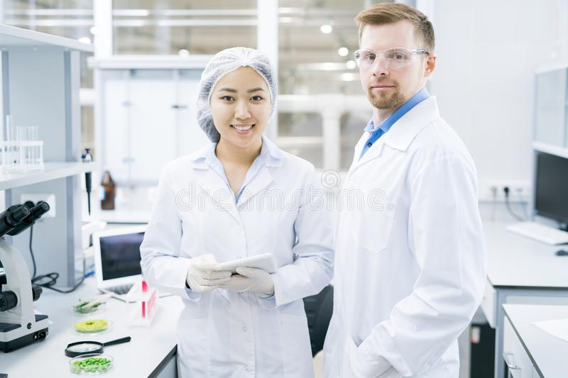Smiling microbiologists standing in laboratory with tablet royalty free stock photos