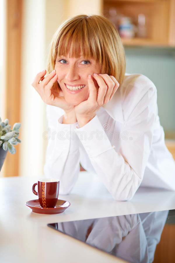 Smiling mid aged woman with a cup of coffee stock image