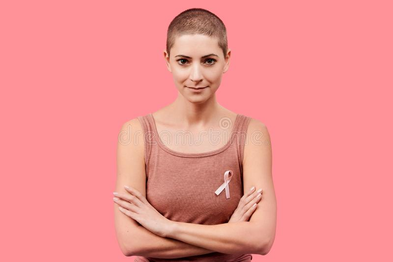 Smiling mid 30s woman, a cancer survivor, wearing pink breast cancer awareness ribbon, isolated over living coral background. Support, solidarity, screening royalty free stock photos