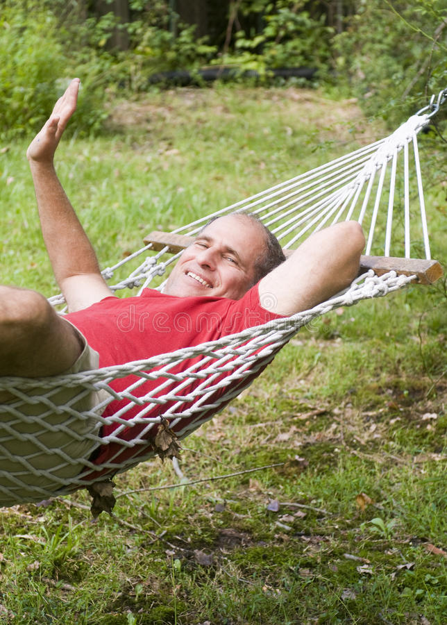 Smiling middle age man relaxing in hammock. In suburban backyard stock photos