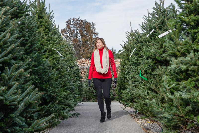 Happy woman on Christmas tree lot royalty free stock image