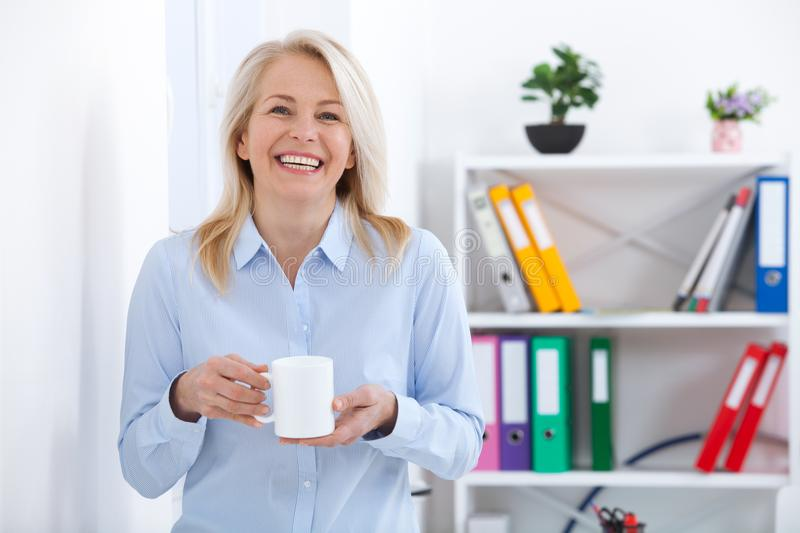 Smiling middle aged businessman with a cup of coffee in the office. Coffee break. stock images