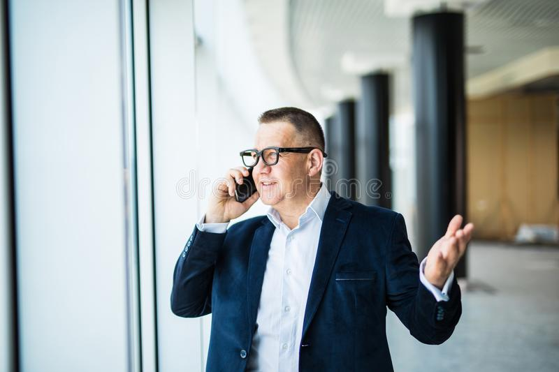Smiling middle aged businessman using phone sitting in front of window overlooking cityscape royalty free stock photos
