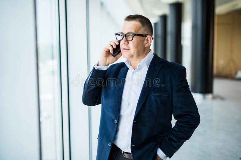 Smiling middle aged businessman using phone sitting in front of window overlooking cityscape stock photography
