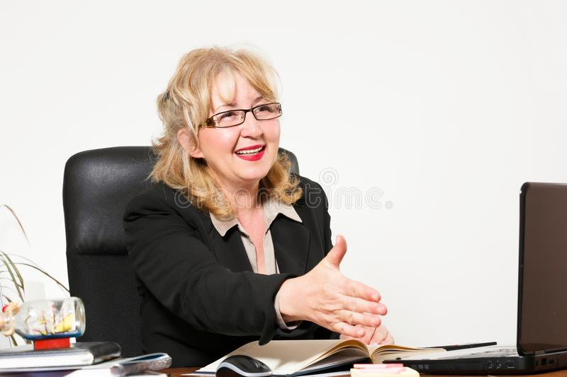Smiling middle aged businesswoman, at the desk. In office royalty free stock photos