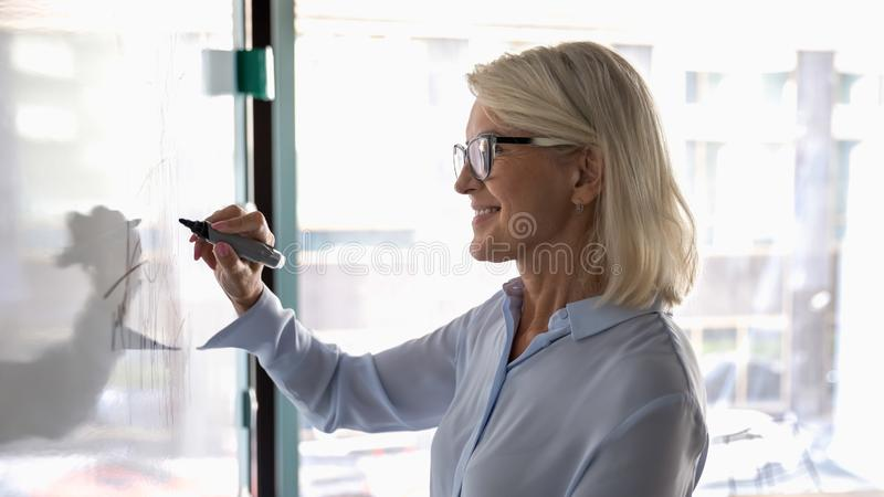 Smiling middle-aged businesswoman draw on board developing startup strategy. Smiling middle-aged Caucasian businesswoman in glasses engaged in creative thinking royalty free stock image