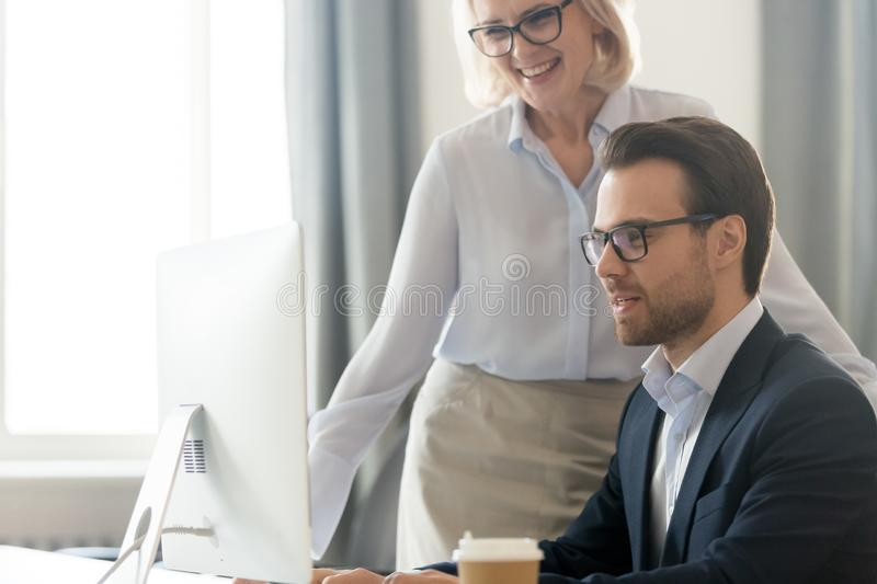 Smiling middle-aged businesswoman help male employee working on pc. Smiling middle-aged businesswoman monitor male employee work online at pc in office, happy stock photography