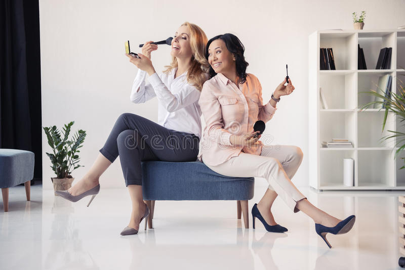 Smiling middle aged businesswomen sitting together and applying makeup in office stock photos