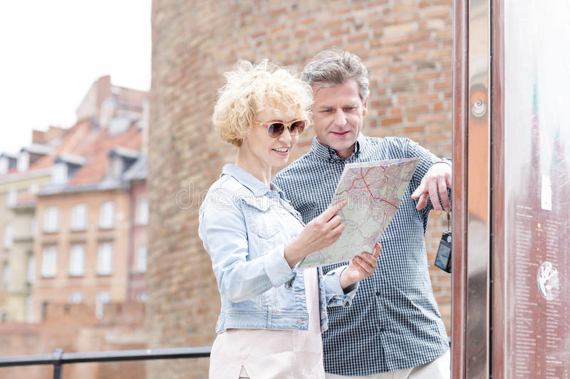 Smiling middle-aged couple reading map in city stock photography