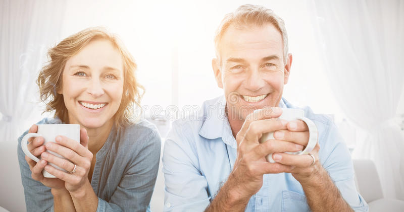 Smiling middle aged couple sitting on the couch having coffee stock photo
