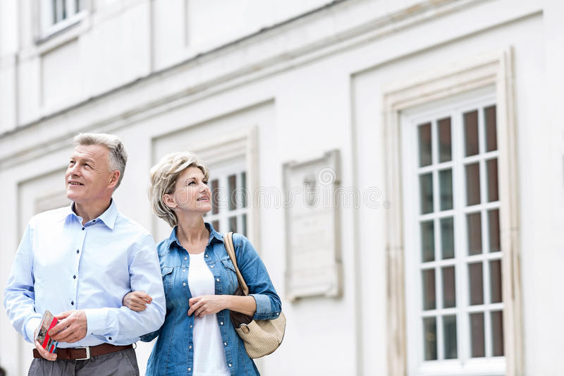 Smiling middle-aged couple standing with arm in arm outside building royalty free stock image
