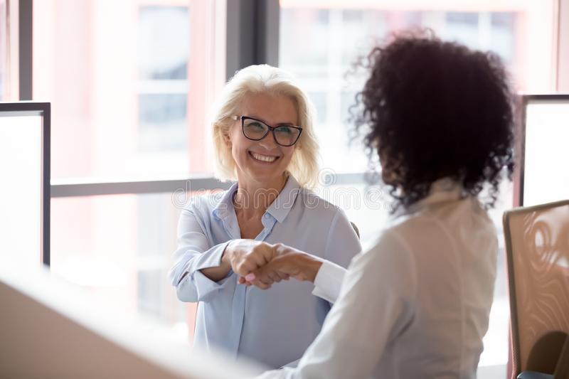 Smiling middle-aged female employee handshake colleague in office stock photography