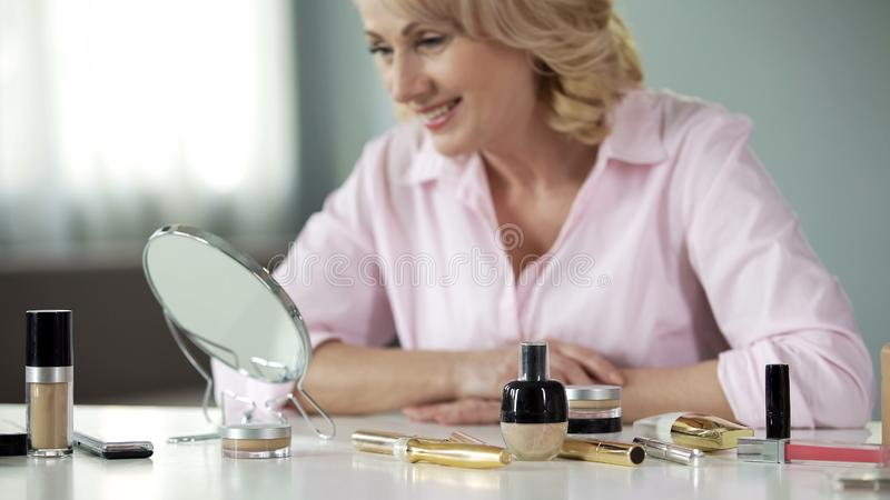 Smiling middle-aged lady looking mirror, anti-wrinkle cosmetology, beauty care. Stock photo stock images