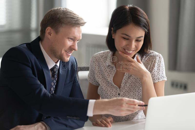 Smiling middle aged team leader helping korean female happy intern. royalty free stock image