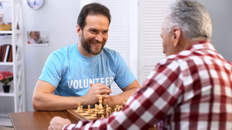 Smiling middle aged male volunteer playing chess with senior man in nursing home stock image