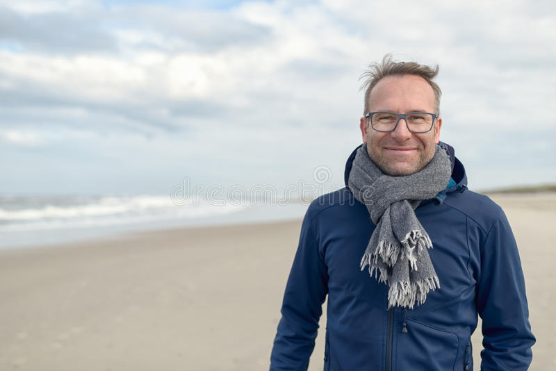 Smiling middle-aged man on an autumn beach. Smiling middle-aged man wearing glasses and a knitted woollen scarf standing on a deserted autumn beach on a cloudy stock photo