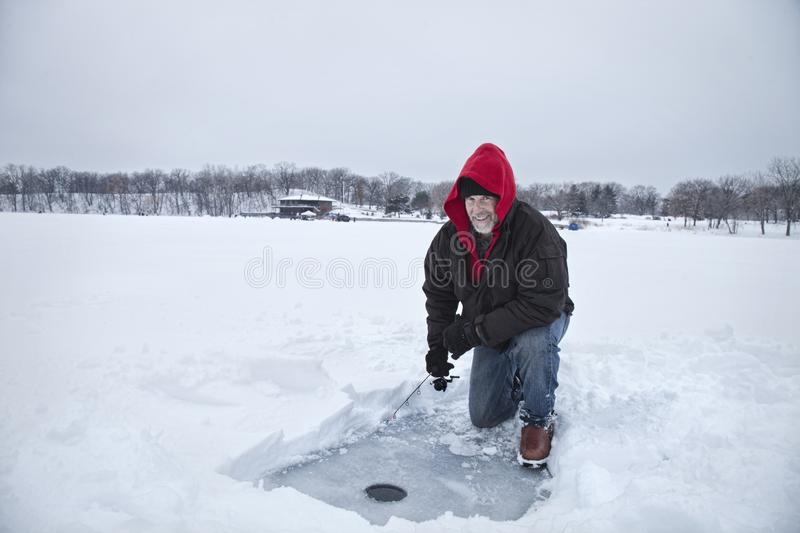 A smiling middle aged man ice fishing on a lake in Minnesota during winter stock images