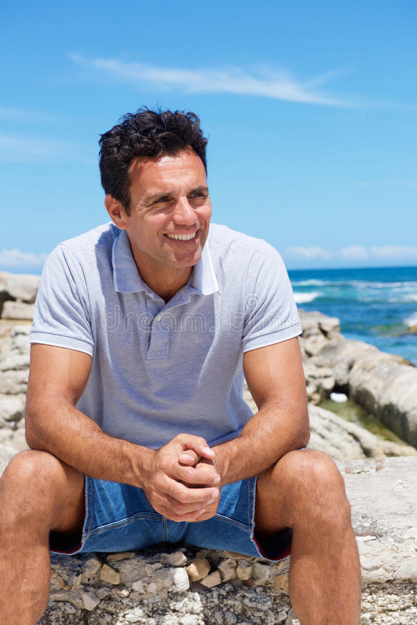 Smiling middle aged man sitting by the beach. Portrait of a smiling middle aged man sitting by the beach royalty free stock images