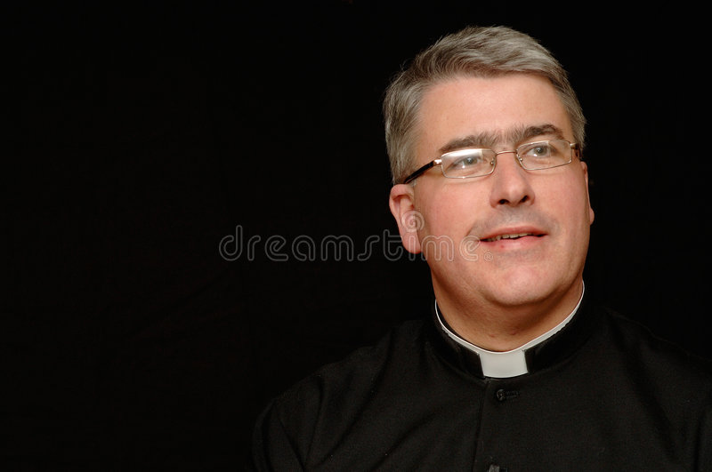 Smiling middle aged priest stock image