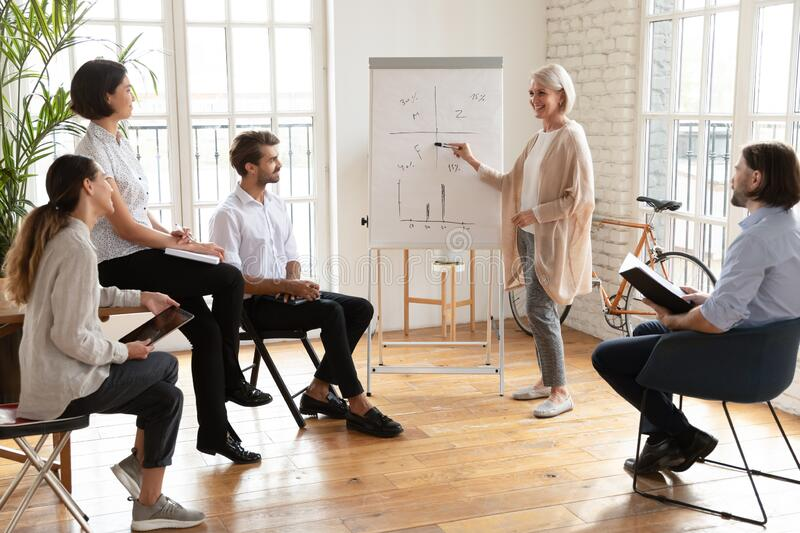 Smiling middle-aged speaker make whiteboard presentation in office royalty free stock photography