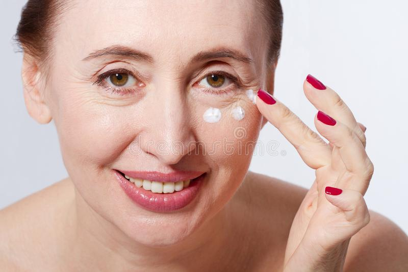 Smiling Middle aged woman applying cosmetic cream by finger on her face, white background. Macro and selective focus. Menopause an stock photos