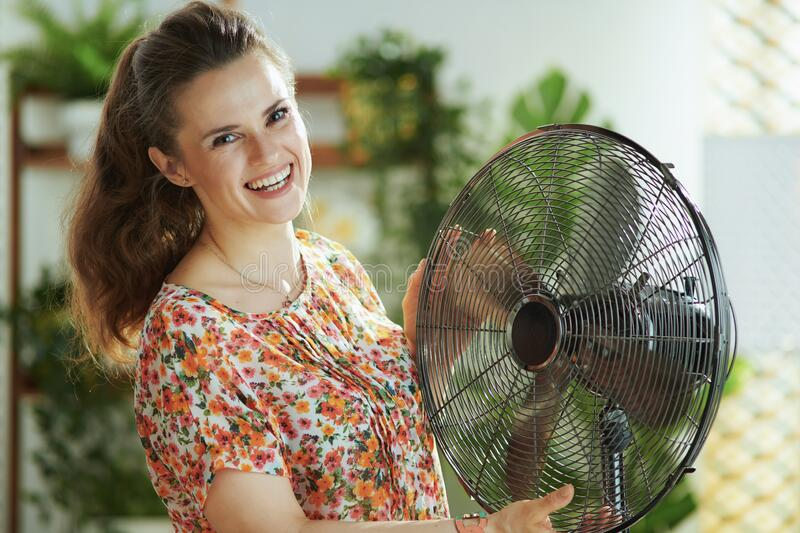 Smiling middle aged woman with electric fan royalty free stock image