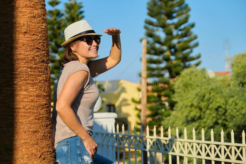Smiling middle-aged woman enjoying vacation in tropical seaside resort stock photography