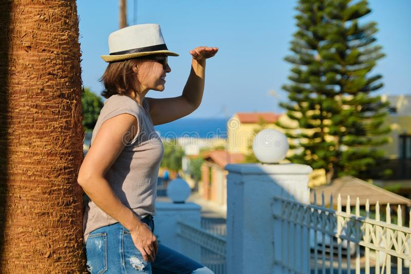 Smiling middle-aged woman enjoying vacation in tropical seaside resort stock photo