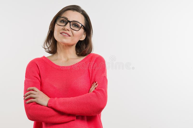 Smiling middle aged woman with folded arms. white background. Smiling middle aged woman with folded arms on white background royalty free stock photography