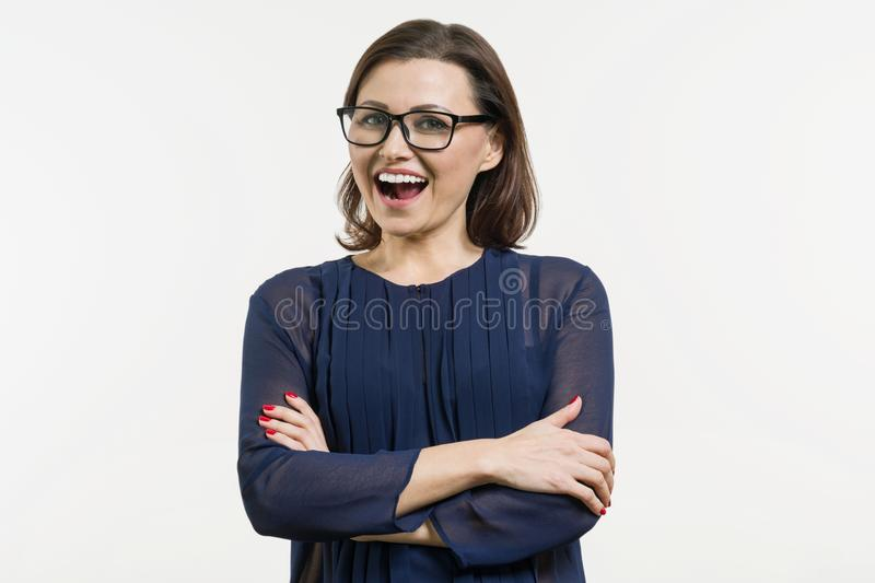Smiling middle aged woman with folded arms on white background.  royalty free stock images