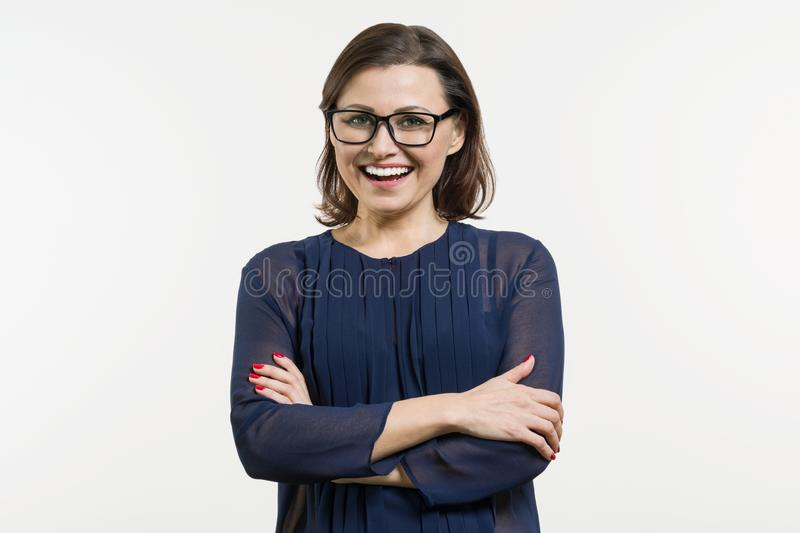 Smiling middle aged woman with folded arms on white background royalty free stock photos