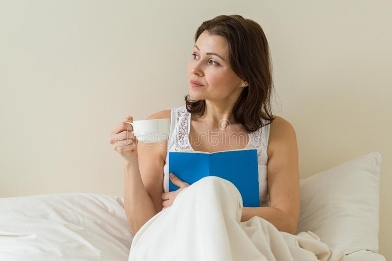 Smiling middle-aged woman reading book and holding cup with coffee on the bed stock photos