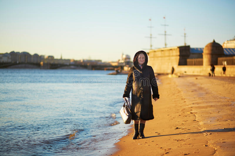 Smiling middle aged woman in St. Petersburg, Russia on a winter day. Smiling middle aged woman in St. Petersburg, Russia on a sunny winter day without snow royalty free stock images
