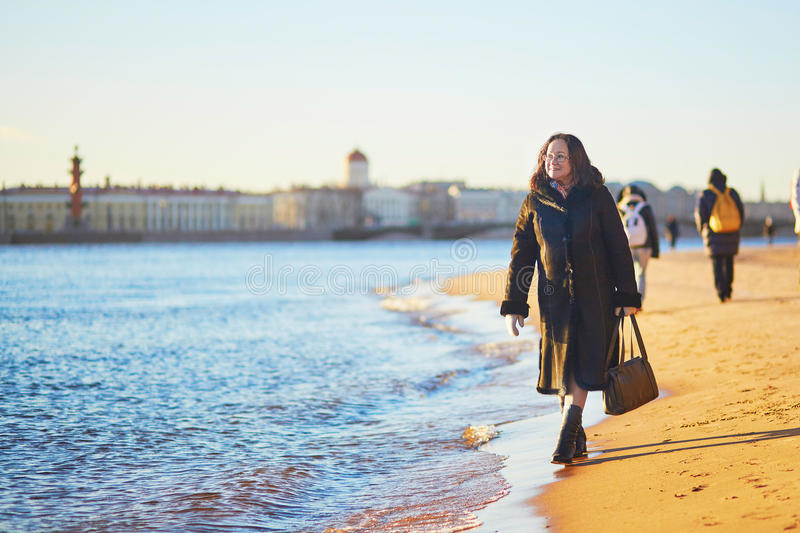 Smiling middle aged woman in St. Petersburg, Russia on a winter day. Smiling middle aged woman in St. Petersburg, Russia on a sunny winter day without snow royalty free stock photo
