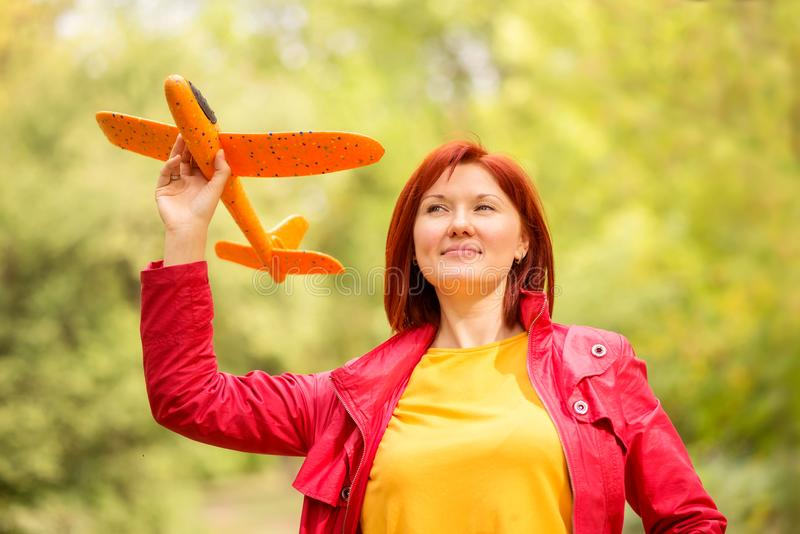 Smiling middle-aged woman standing in autumn park holding toy airplane and looking up in the sky. Power of dreams concept stock photo