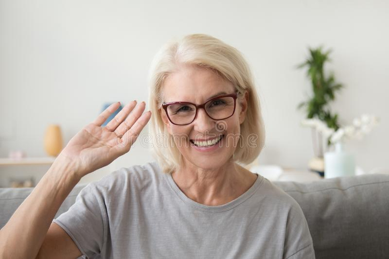 Smiling middle aged woman waving hand looking at camera, portrai stock photo