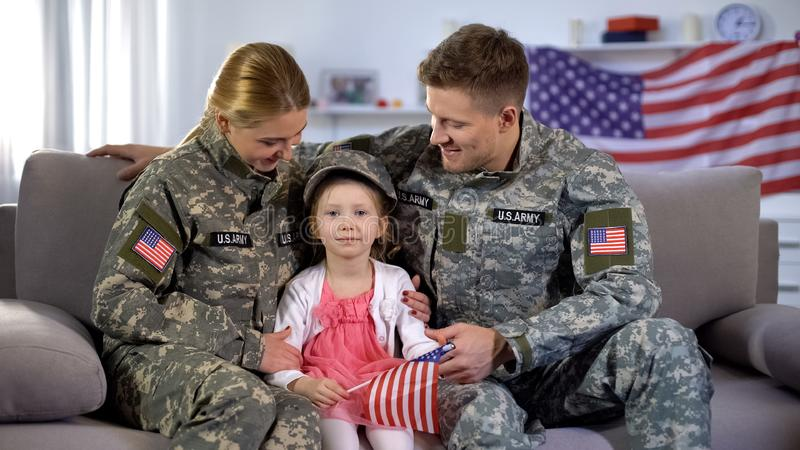 Smiling military parents looking at cute daughter with american flag, patriots. Stock photo stock images