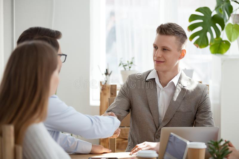 Millennial businessman handshake male employee at briefing. Smiling millennial businessman sit at table heading meeting shaking hand of male colleague, employees stock photography