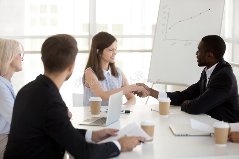 Smiling millennial caucasian businesswoman and african partner h. Smiling millennial caucasian businesswoman and african partner shake hands at office group stock images