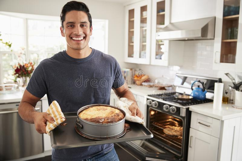 Smiling millennial Hispanic man standing in kitchen presenting the cake he has baked to camera royalty free stock photo