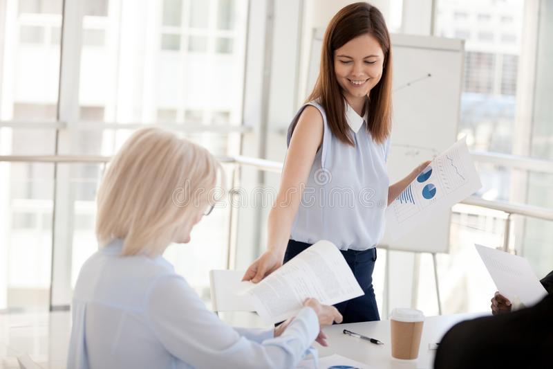 Smiling millennial mentor share handouts to employees at briefin royalty free stock photo
